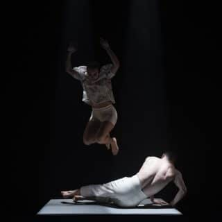 One dancer is jumping mid air above a second dancer who is lying on the floor, attempting to get up. From Brink, 2020, commissioned by Maiden Voyage Dance Company. Photo Credit Luca Truffarelli