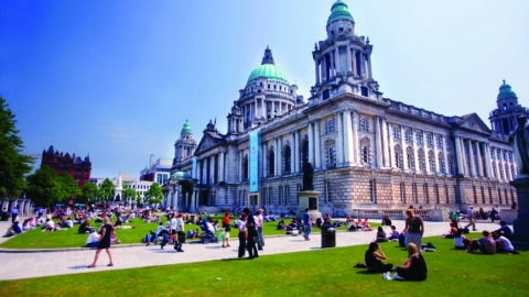 Belfast City Hall in summer, with groups of people sitting on the lawns enyoing the sunshine. Courtesy of Tourism NI