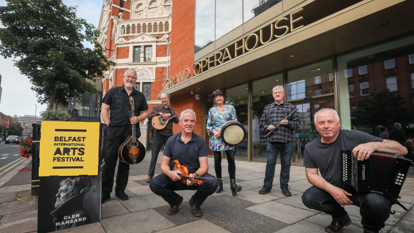 Dervish launch Belfast International Arts Festival 2021 programme. Members of the folk band are posing with their musical instruments outside Grand Opera House, Belfast.