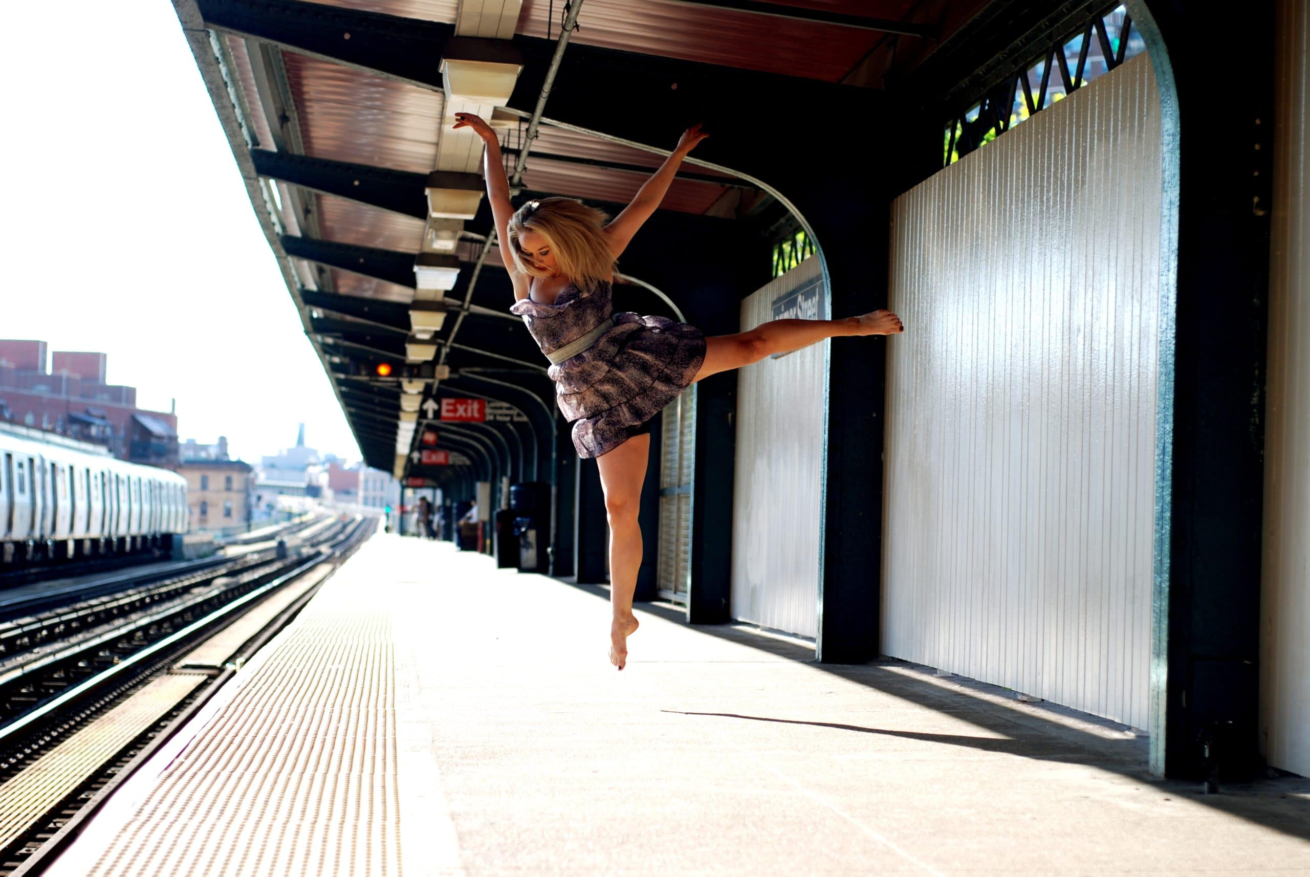 Dancer Eileen McClory in a graceful outstretched jump pose, taken on an empty train platform. Photo Credit Molly Craycroft