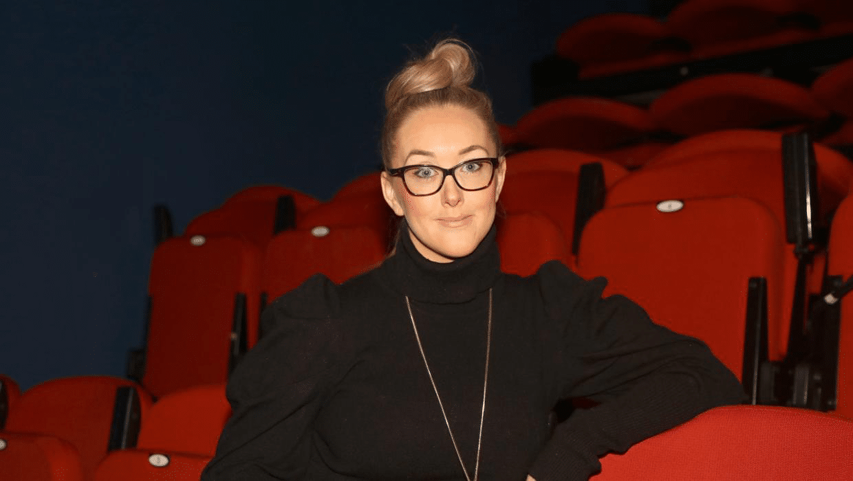 Eileen McClory, who is seated in a theatre auditorium. She is wearing a black jumper, long gold chain and black rimmed glasses.