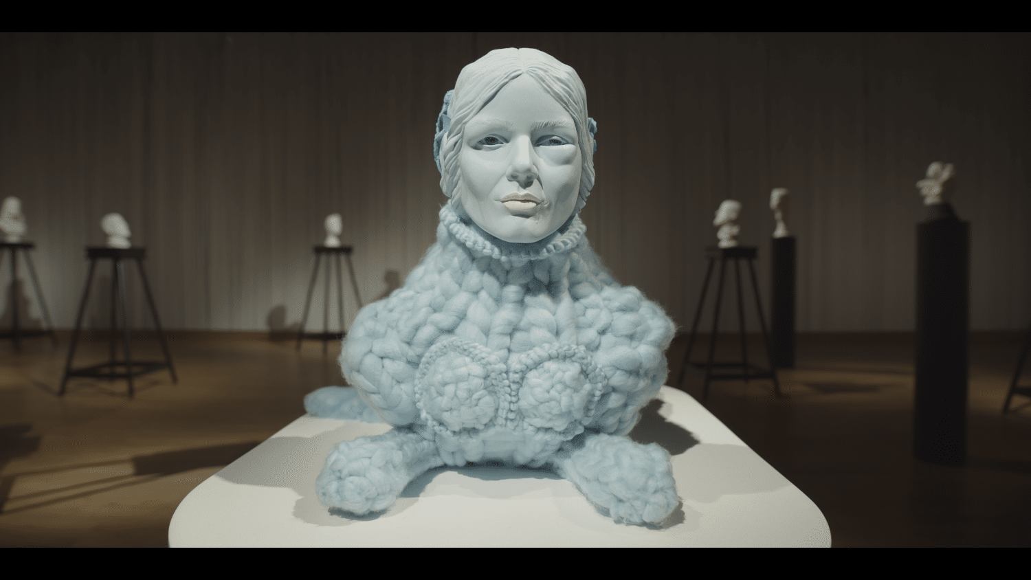 Sculpture of a bust of a woman, with a patterned knitted woollen collar. Made by Ursula Burke. Backdrop to Madrigals At The Museum performance